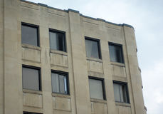Beige concrete building habitation or office place downtown. Concrete building office windows downtown apartment Royalty Free Stock Images