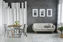 Beige couch against concrete wall. Elegant beige couch against concrete wall in open space dining room with wooden table and gray chairs Stock Image