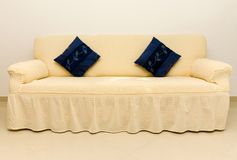 Beige couch and blue cushions. Beige couch with two blue cushions Royalty Free Stock Photography