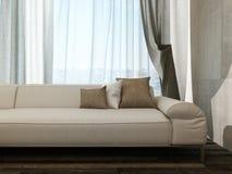 Beige Couch gegen Vorhänge Stockfoto