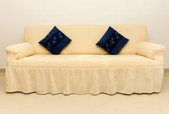 Beige Couch und blaue Kissen. Lizenzfreie Stockfotografie
