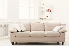 Beige couch on white window background. Beige couch with pillows in white modern interior, copy space on window background. Contemporary apartment design Stock Photos