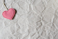 Beige crumpled paper with heart for valentine background. Royalty Free Stock Images
