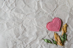 Beige crumpled paper with heart and withered leaves for valentin Royalty Free Stock Images