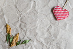 Beige crumpled paper with heart and withered leaves for valentin Stock Images
