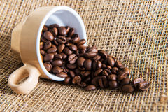 Beige cup with coffee seed on jute bag Stock Photo