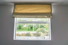 Beige curtain at the window in bedroom Stock Image