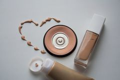 Beige dashed heart with dry and liquid skin tone correctors stock image