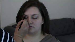 Beige die oogschaduw op jonge vrouw wordt geborsteld stock video