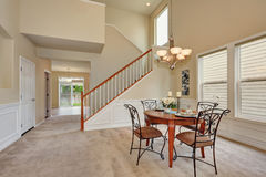Beige dining room interior with high ceiling and staircase Royalty Free Stock Photography
