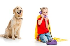 Beige dog with smiling little supergirl talking on phone and wearing yellow cape stock images