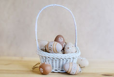 Beige easter eggs  in small white  basket Royalty Free Stock Images