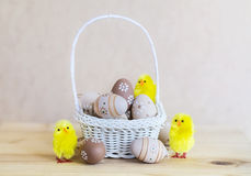 Beige easter eggs  in small white  basket Royalty Free Stock Photos