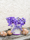 Beige easter eggs and vase with  violets Royalty Free Stock Photo