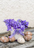 Beige easter eggs and vase with  violets Royalty Free Stock Images