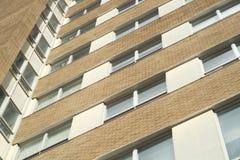 Beige Eckziegelstein des Gebäudes und Fensterbürowolkenkratzer Lizenzfreie Stockbilder