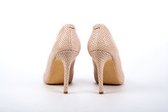 Beige elegant ladies` high-heeled shoes on a white background Royalty Free Stock Image