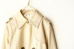 Beige elegant trench coat isolated over white. A beige elegant trench coat isolated over white. Close up Stock Image