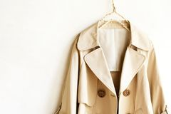 Beige elegant trench coat isolated over white. A beige elegant trench coat isolated over white. opened in front. Close up Royalty Free Stock Images