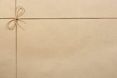 Beige emballagepapper, skyler över brister bundet med ett rep Royaltyfri Foto