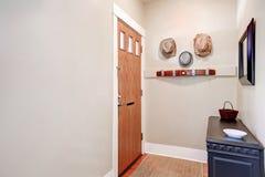 Beige entryway med kabinettet, spegel, hattar som hänger på väggen royaltyfria bilder