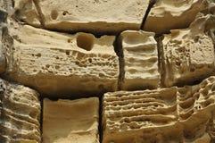 beige eroderade gammala stenar Arkivfoto