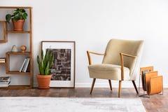 Beige fåtölj bredvid affischen och växten i den vita lägenheten som är inre med matta och hyllor Verkligt foto arkivfoto