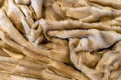 Beige f aux fur many random folds create interesting texture. A beige f aux fur blanket folded in a way to create many random folds and textures stock photos