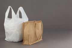 Beige fabric bag and white plastic bag. Against grey background Stock Photography