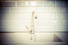 Beige faucet in the kitchen. On a background of white tiles Stock Photos