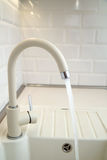 Beige faucet in the kitchen. On a background of white tiles Royalty Free Stock Images