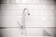 Beige faucet in the kitchen. On a background of white tiles Royalty Free Stock Photography