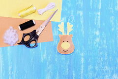 Beige felt reindeer ornament, scissors, thread, needle, cord, filler, felt sheets on blue wooden background Royalty Free Stock Image