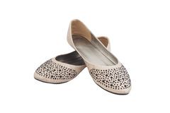 Beige flat lady's shoes with black plastic jewelry Royalty Free Stock Photos