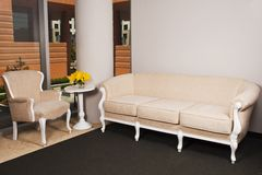 Beige furniture in large room. Beige furniture with yellow flowers set up in a room royalty free stock image