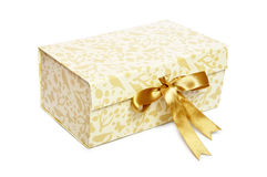 Beige gift box. With golden ribbon over white background Royalty Free Stock Photo