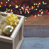 New year suprise in a box with on a colored wooden background. A beige gift box with a golden bow and a gold ball and a snowflake and cookies in a wooden drawer Stock Photo