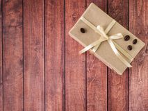 Beige giftdoos met lint en boog op houten achtergrond, plaats voor het van letters voorzien stock foto