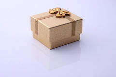 Beige/Golden gift box. A view of a small beige/golden or tan gift box with a decorative golden bow attached.  Box isolated Royalty Free Stock Image