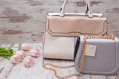 Beige and gray bags on a wooden background, pink tulips. Fashionable concept.  Royalty Free Stock Image