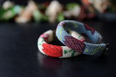Beige and gray beaded bracelets with flower print on a dark background. Close up Stock Images