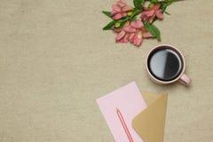 Beige hantverkkuvert med mellanrumet, blommor, kopp kaffe på stenbakgrund royaltyfri bild