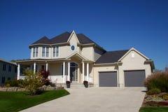 Beige Haus mit emporgeragtem Dach. Lizenzfreie Stockfotos