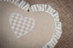 Beige heart-shaped pillow for home against the background of burlap sofa royalty free stock photography