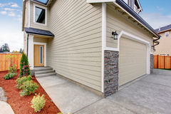 Beige house with concrete walkway to the entrance door. Stock Image