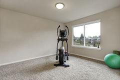 Beige interior of small home gym with sport equipment Stock Photography