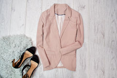 Beige jacket business style, black shoes with gray fur. Fashionable concept, wooden background, top view Stock Photography