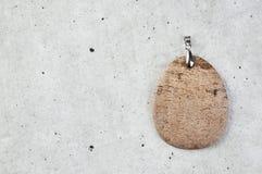 Beige jasper pendant on a gray background. Stock Photos
