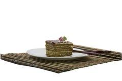 Beige kaka på en vit platta, på en filt, med pinnar Arkivbilder
