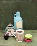 Beige Knitted Mug, Macaroons, Blue Bottle And Rough Paper Bag Background On Green Grunge Background. Nude Still Life. Stock Photography